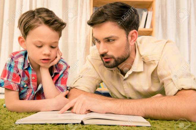 Close up portrait of father teaching his son to read book